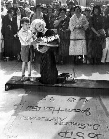Harlow with a young fan outside of Grauman's Chinese Theater in 1933.