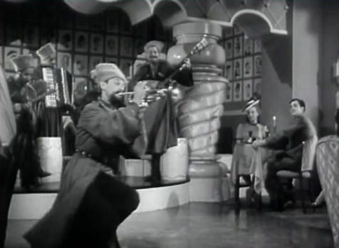 Astaire, dressed as a Cossack, does the Cossack dance while playing the trumpet. (Comet Over Hollywood/ Screencap by Jessica Pickens)