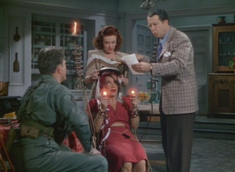 Due to Carmen Miranda's short wave radio tooth-she is being used to send Morse Code. Also pictured-Michael O'Shea, Vivian Blaine, Phil Silvers. (Comet Over Hollywood/Screen cap by Jessica P.)