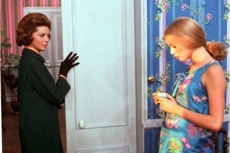 Vernon and Deneuve (as Genvieve). Deneuve's dress matches the bright wallpaper