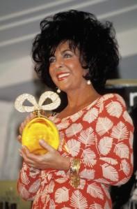 Elizabeth Taylor Holding Perfume Bottle