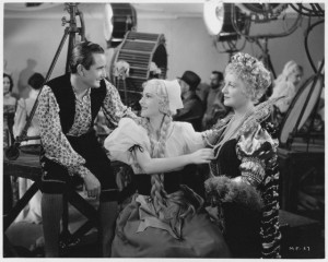 "Nino Martini, Joan Fontaine, and Lee Patrick (left to right) work as Hollywood film extras in ""Music for Madame."""