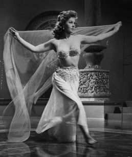 "Hayward shows off her figure as she dances in the John Wayne film ""The Conqueror"" (1954)."