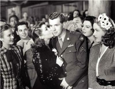 Slim (Hutton) receives a kiss from his actress crush Joan Leslie at the Hollywood Canteen.