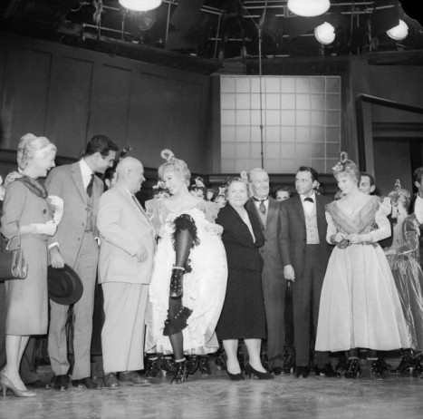 Shirley MacLaine performs like a Can Can girl for Soviet Premier Nikita Khrushchev at the 20th Century Fox Studios. Left to right: Louis Jourden, Mr. Khrushchev, Shirley MacLaine, Mrs. Khrushchev, Maurice Chevalier, and Frank Sinatra.