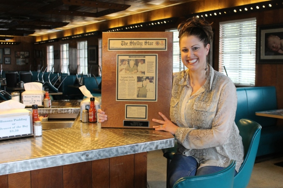 (The Star/Jessica Pickens) Natalie Ramsey, VP of Red Bridges Barbecue, remembers when Mickey Rooney visited the restaurant in 1997. She holds a Shelby Star article that hangs in the restaurant.