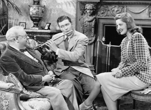 Dennis Morgan shows S.Z. Sakall and Martha Vickers how to play swing on the flute.