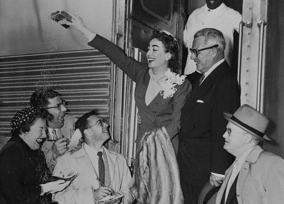 Joan Crawford throwing rice with new husband Alfred Steele. Crawford said Youth Dew helped her attract him.