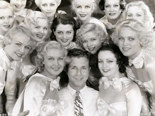 "Publicity photo of Dick Powell and several ""Dames."""