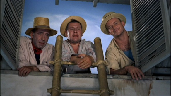 The three convicts watch the family from the roof.