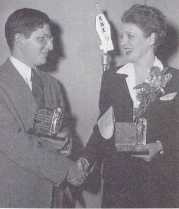 "Actress Mary Astor presents Bernard Herrmann with the Academy Award for Best Score for ""All That Money Can Buy."""