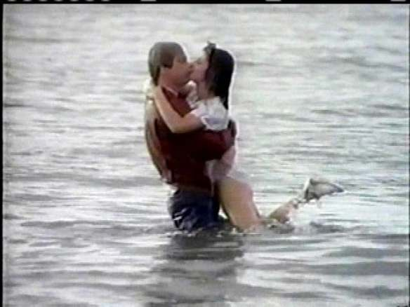 Gidget and Moondoggie kissing in the ocean with their clothes on.